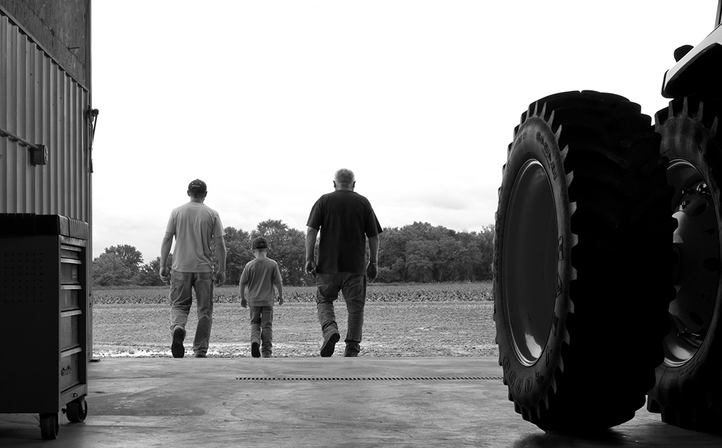 Generations of Farmers Walking Next to Tractor