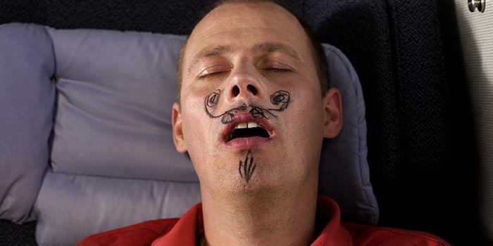A sleeping man who has had a mustache drawn on his face.