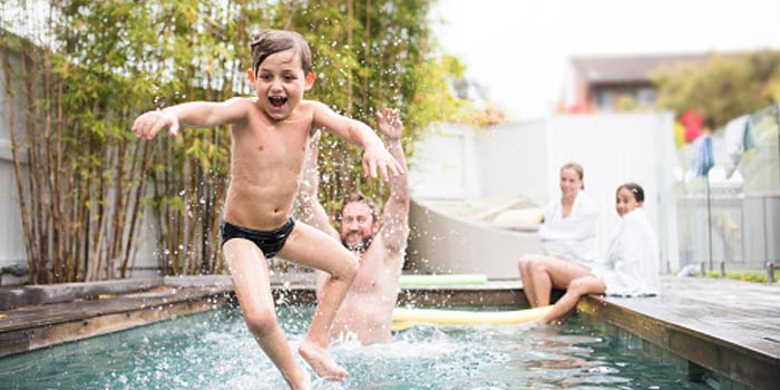 A young boy jumps into his family pool while his family watches him.