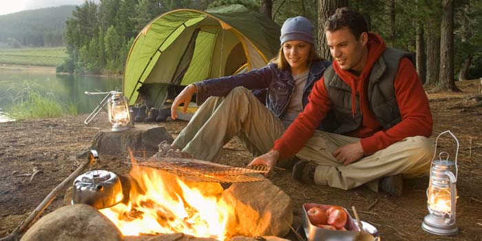 A man and a woman cooking on a campfire in a forest.