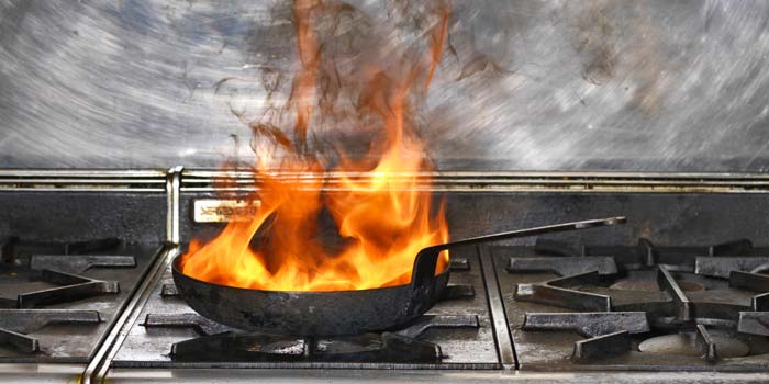 A pan on fire on a stove, one of the six causes of fires in the home.