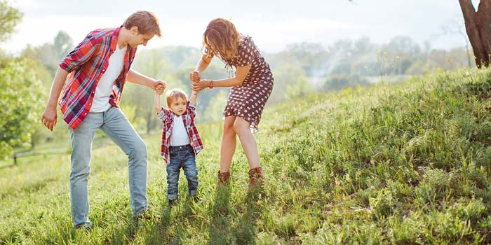 A mother and father help their toddler walk on a hill in the country.