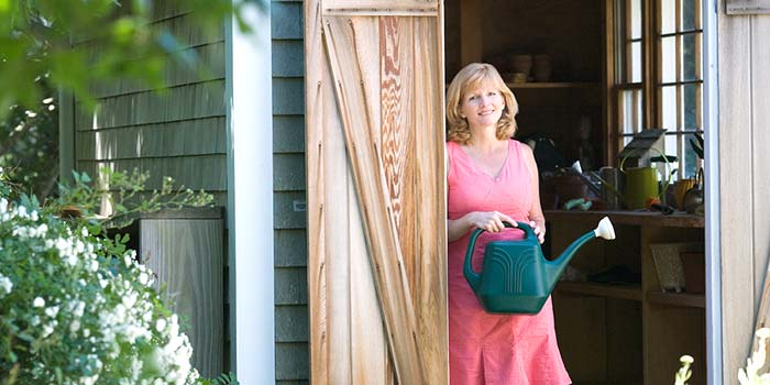 Woman holding a watering can in the door of her gardening shed