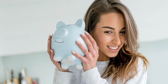 A woman shakes a piggy bank by her ear to see if there are coins inside.