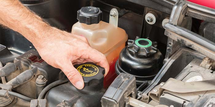 A man's hand begins to open the oil cap on the engine of a car.
