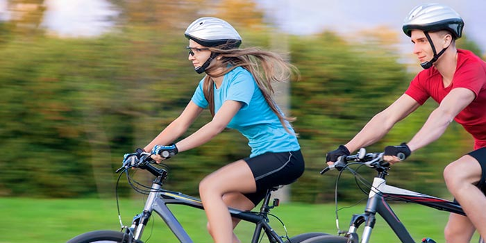 Two young people in proper safety gear enjoying a bike ride.