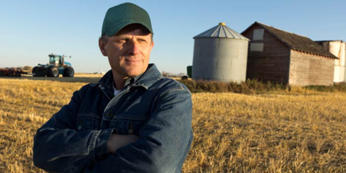 A farmer stands in a harvested field, with a tractor and barn behind him.