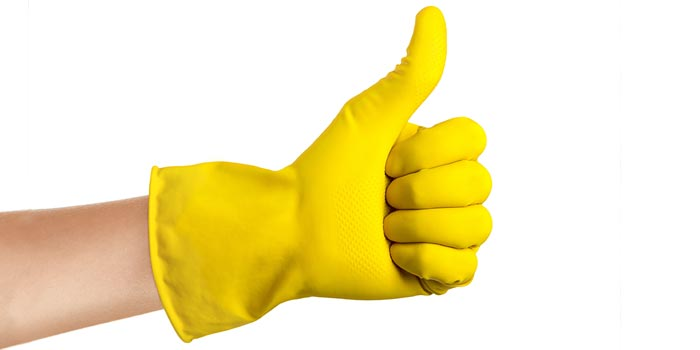 A hand wearing a yellow glove giving a thumbs up.