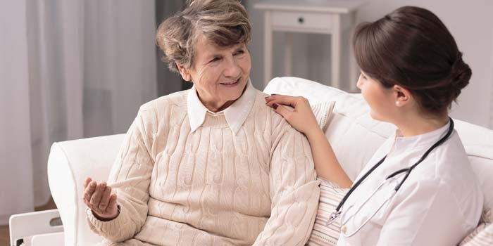 Elderly woman talking to a home health care provider.