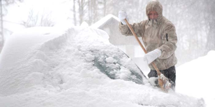 A man removes snow from his car during a blizzard.