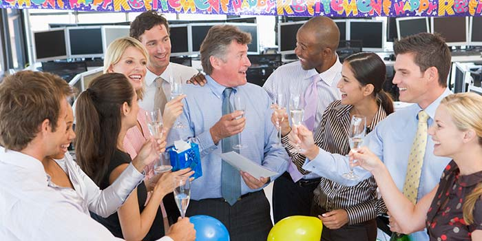 A group of office workers celebrating a fellow employee's retirement.
