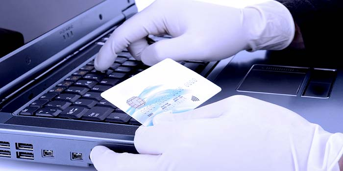 Man wearing rubber gloves, holding a credit card and typing the card numbers into a laptop