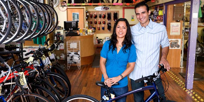 A man and woman posing in in their bicycle shop.