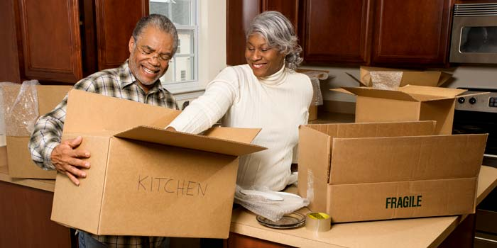 Two retirees packing boxes in their kitchen.
