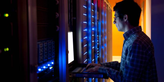 An IT engineer configures a bank of servers.