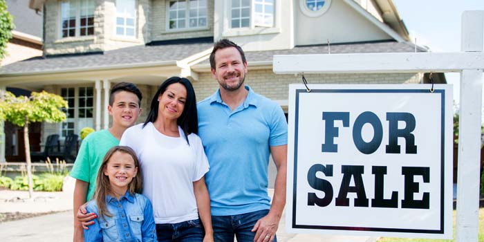 "A family standing outside their house, next to a ""For Sale"" sign."