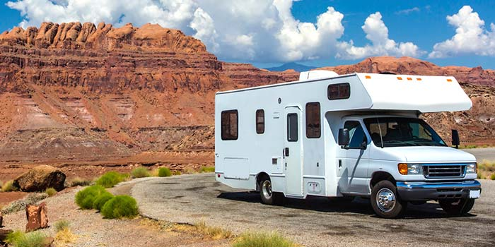 A motor home parked by scenic mountains in the US Southwest.