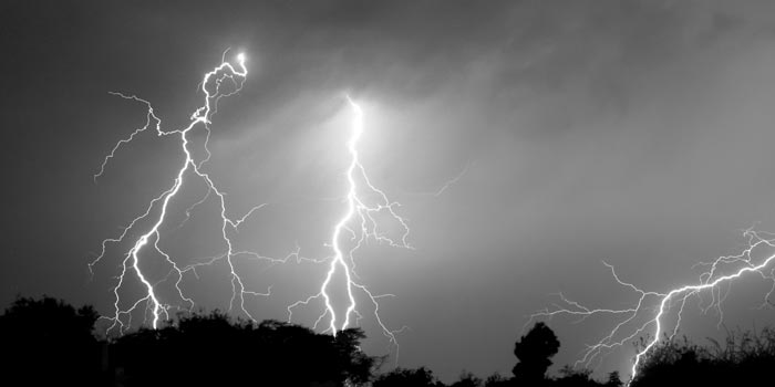 Bolts of lightning streak across a darkened sky.