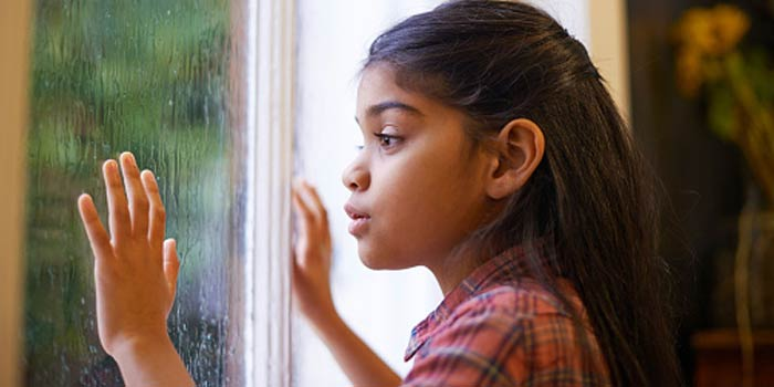 A young girl looking anxiously through a window at the storm outside.