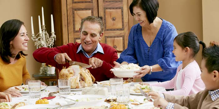 A multi-generational family sitting around a table enjoying Thanksgiving dinner.