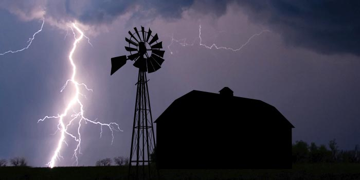 A lightning storm rages in the night sky behind a farm in silhouette.