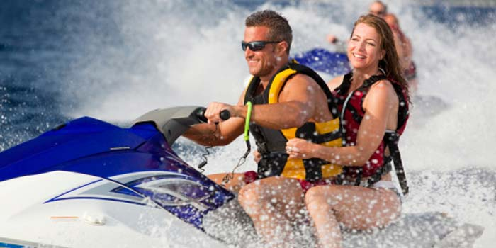 A man and woman safely operate a jet ski in the ocean.