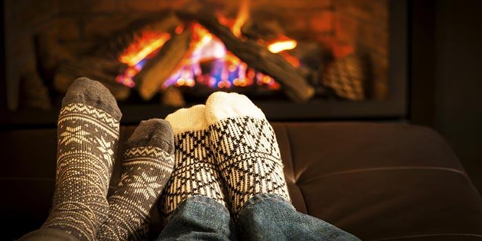 Two people resting their feet by a roaring fireplace.