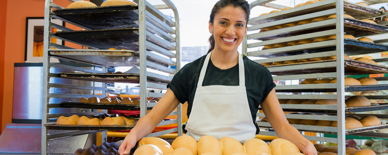 Businesswoman carrying pan of bread through bakery