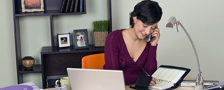 Woman working at desk in her home-based business