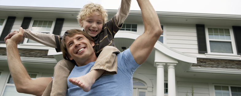 Male homeowner with son on his shoulders in front of house