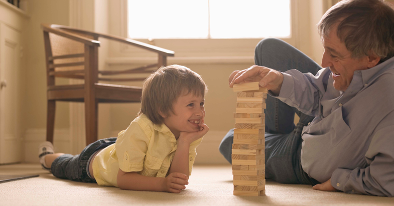 Grandfather and grandson playing Jenga on the floor