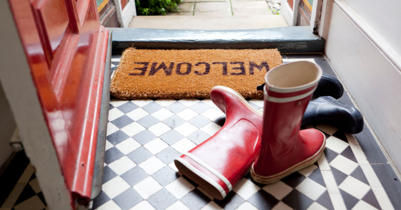 Home entryway with welcome mat and boots on floor
