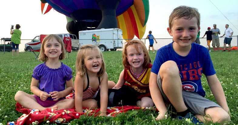 Four young children laughing in the grass at a hot air balloon event.