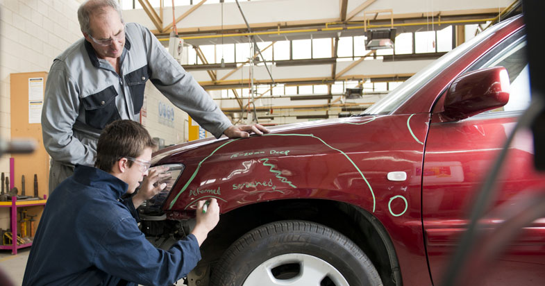 Mechanics at auto repair shop fixing dented car